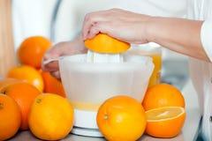Preparation of citrus juice. Preparation of orange juice on   mechanical manual juicer stock image