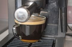 Preparation of coffee for Breakfast in a carob coffee maker, a Cup of black coffee with foam.  stock image
