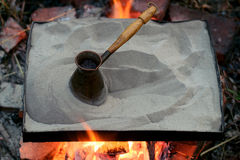 Preparation of coffee in a turk on sand on a fire in the open air Royalty Free Stock Image