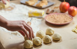 Preparation cookies with cinnamon, cottage cheese and apples on kraft paper. Female hands rolling dough in meals Stock Images