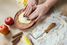 Preparation cookies with cinnamon, cottage cheese and apples on kraft paper. Female hands rolling dough in sugar Royalty Free Stock Images