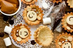 Preparation cookies shaped monkey face, ingredients and finished stock photos