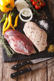 Preparation for cooking raw duck breast with vegetables and spic. Es close-up on the table. vertical Royalty Free Stock Photo