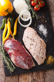 Preparation for cooking raw duck breast with vegetables and spic. Es close-up on the table. Vertical view from above Stock Images