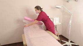 Preparation of a cosmetology chair for the procedure shugaring. The cosmetologist covers a chair for sugaring with a disposable sterile diaper before the stock video footage
