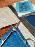 Preparation for cuttings for cards. Measures for handicrafts: scissors,  rule and beautiful sheets of cartons Royalty Free Stock Image