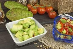 Preparation of dietary avocado salad. Fresh ripe avocado on a wooden background. Royalty Free Stock Images