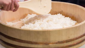 Preparation for doing sushi. Look at this rice. Asian chef standing in kitchen of sushi bar mixing rice in big wooden bowl with help of wooden spoon preparing it stock video footage