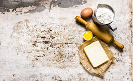 Preparation of the dough. Ingredients for the dough - Flour, eggs, butter with a rolling pin. Stock Photo