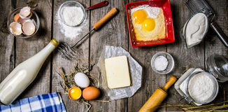 Preparation of the dough. Ingredients for the dough - milk, cream, butter, flour, salt, eggs and different tools. On a wooden table.  Top view Stock Photos