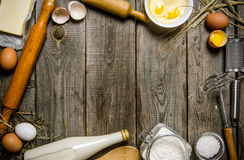 Preparation of the dough. Ingredients for the dough - milk, flour, eggs and different tools . On a wooden table.  Free space for text . Top view Royalty Free Stock Image