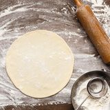 Preparation of the dough. Rolled out pizza and rolling pin. On flour, top view, crop stock photography