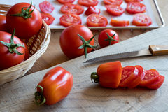 Preparation of dried tomatoes - slicing San Marzano tomatoes. On a cutting board Stock Photography