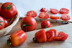 Preparation of dried tomatoes - slicing San Marzano tomatoes. On a wooden table Stock Photo