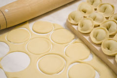 The preparation of dumplings. Roll out the dough with a rolling pin and mold dumplings with meat Stock Image