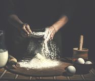 Man preparing bread dough on wooden table in a bakery close up. Preparation of Easter bread. Stock Image