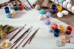 Preparation for Easter. Colorful handmade Easter eggs, paint, brushes on a white wooden background tabel royalty free stock image