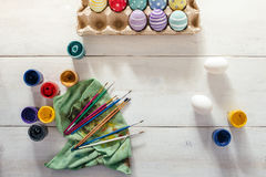 Preparation for Easter. Colorful handmade Easter eggs, paint, brushes on a white wooden background tabel. Top view. Flat lay sty Stock Photos