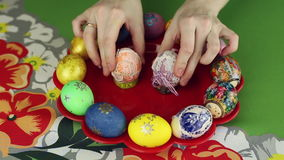 Preparation of easter eggs, the feast of the passover. Girl puts decorated Easter eggs on a tray stock video