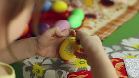 Preparation of Easter eggs, the feast of the passover. Girl sticks decorative stickers on the Easter eggs stock video footage