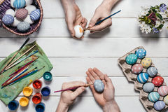 Preparation for Easter. Human hands paint Easter eggs with brushes and paints on an old white wooden background. Top view. Flat la Royalty Free Stock Images