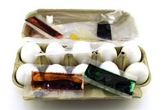 Preparation for Easter, white chicken eggs in a box and bags of colorful paints for eggs on a white background stock photo