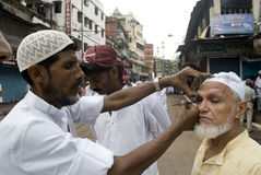 Preparation for Eid Prayer. A Muslim man is putting eye makeup to an old Indian Muslim before Eid prayer at Kolkata Stock Image