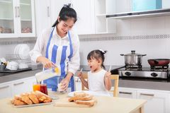 preparation of a family breakfast. Asian mother and baby daughter cook breakfast in morning. royalty free stock photo