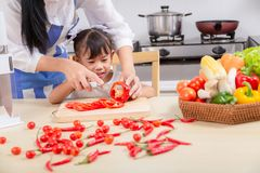 Preparation of a family breakfast. Asian mother and baby daughte. R cook breakfast in morning royalty free stock photos