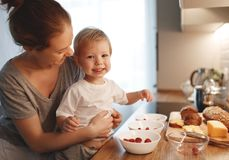 Preparation of family breakfast. mother and baby son cook porrid Royalty Free Stock Photo