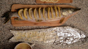 Preparation of fish with lemon in oil. Pike with cuts, slices of lemon are inserted into the incisions. Everything is smeared with butter and falls into a foil stock footage