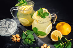 Preparation of a fresh lemonade cocktail. Lemonade in the jug and lemons with mint Stock Photo