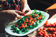 Preparation of fresh salad with tomato, ruccola on a kitchen table. Stock Photo
