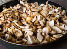 Preparation of fried mushrooms and onion in a frying pan Royalty Free Stock Image