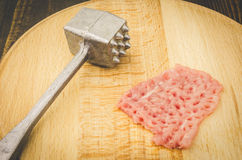 Preparation for frying raw chop. Raw chop on a cutting wooden board Stock Image