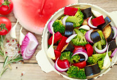 Preparation garnish. Raw fresh vegetables - broccoli, eggplant, bell peppers, tomatoes, onions, garlic Royalty Free Stock Photos
