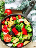 Preparation garnish. Raw fresh vegetables - broccoli, eggplant, bell peppers, tomatoes, onions, garlic in a cast iron frying pan Royalty Free Stock Photography