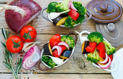 Preparation of the garnish. Raw fresh vegetables - broccoli, eggplant, peppers, tomatoes, onions, garlic in portion pots. Raw fresh vegetables - broccoli Royalty Free Stock Photography