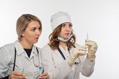 Preparation for giving an injection by the young health workers. Preparation for giving an injection under an instructor`s control Royalty Free Stock Photos