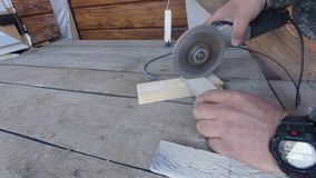 Cutting decorative tiles to the desired size with an angle-grinder. Preparation for gluing tiles on a wooden bar to preserve the cleanliness of the house stock video footage