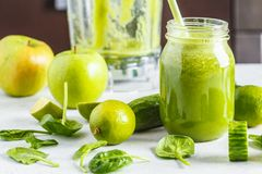 Preparation of green smoothie from spinach, apple and cucumber. Healthy plant based food concept. Preparation of green smoothie on the white table. Healthy plant royalty free stock image