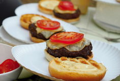Preparation of grilled burger. Beef burger, bun, mayonnaise , cheese, slice of tomato on a paper plate royalty free stock photos