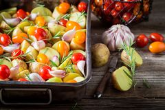 Preparation for grilled homemade potato with garlic, rosemary and tomatoes Stock Photography
