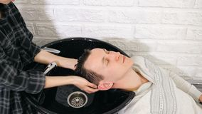Preparation for haircut. Barber washing men`s hair on the head in barbershop.  stock photography