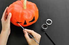 Preparation for Halloween: women`s hands paint orange pumpkin with black paint. Closup. Holiday decoration concept. royalty free stock photos