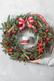 Preparation for holidays concept. Beautiful Christmas wreath in woman hands. Flower shop is a master work of a stock photography