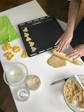 Preparation of homemade cakes. On the table there are flour, butter, baking tray and forms for dough. View from above. A woman rol. Ls out the dough. There is a Royalty Free Stock Photography