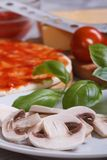 Preparation of ingredients for pizza: sliced ??mushrooms, basil Stock Images