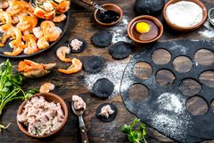 Preparation of Italian black ravioli with seafood shrimps and crabs on black plate, gray stone slate background. Top. View Stock Images