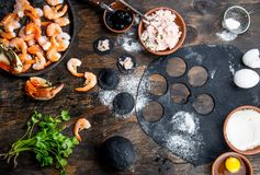 Preparation of Italian black ravioli with seafood shrimps and crabs on black plate, gray stone slate background. Top. View Stock Photography